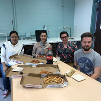 Four research students sitting at a table enjoying a pizza lunch reward