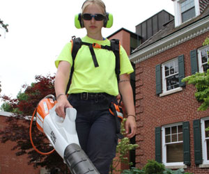 A Landscape Services employee using battery operated blower at Spencer Hall